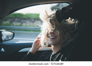 Young blonde woman inside a car with the window open and her hair at the wind