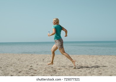 Young blonde woman jogging on the beach. Summer morning recreation by the sea. Active life concept.