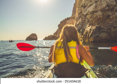 Young blonde woman kayaking alone  in the sea near mountains and holding oar