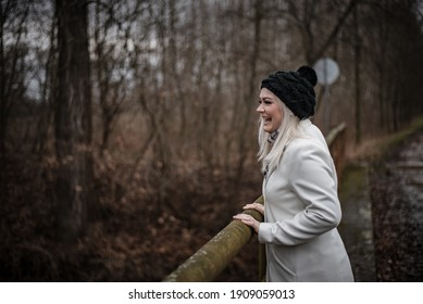 Young blonde woman laughing during winter walk out of town to keep social distance