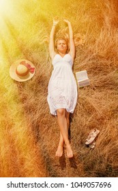 Young blonde woman lies in a golden summer field on dry grass with book. (femininity, beauty, youth, education concept)