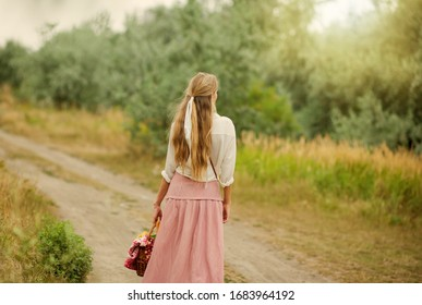 Young blonde woman with long hair in retro style vintage clothes with picnic basket walking on landing