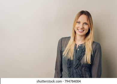 Young blonde woman with long hair, wearing grey blouse standing against plain color light brown wall with copy space, looking at camera and smiling