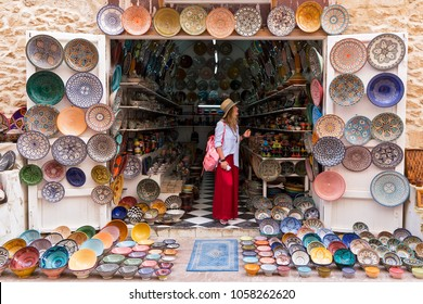 Young blonde woman in a long red skirt, hat and with pink backpack is standing in a small shop and looking at Moroccan colorful plates.