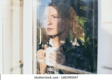 Young blonde woman looking out of the window with a concerned expression on her face.