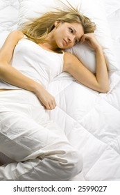 Young blonde woman lying alone in the bed. Looks dreamy.