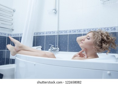 Young blonde woman lying in bath