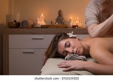 Young blonde woman lying on a massage table. hands applying pressure to his back. concept of well-being