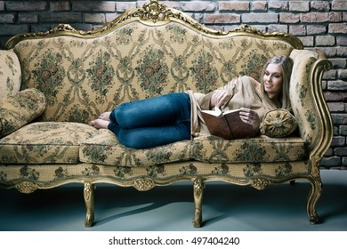 Young blonde woman lying on baroque sofa in stylish home, reading a book.