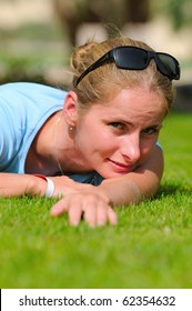 Young blonde woman lying on the grass field