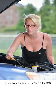 Young blonde woman, missing her left hand, checks the oil in her car - hood lifted, wearing a black tank top