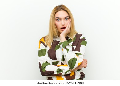 young blonde woman open-mouthed in shock and disbelief, with hand on cheek and arm crossed, feeling stupefied and amazed against white wall