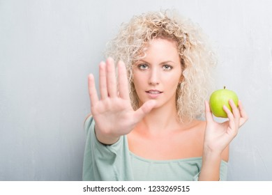 Young blonde woman over grunge grey background eating green apple with open hand doing stop sign with serious and confident expression, defense gesture