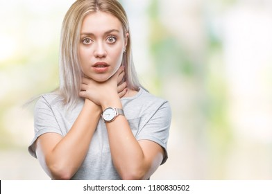 Young blonde woman over isolated background shouting and suffocate because painful strangle. Health problem. Asphyxiate and suicide concept.