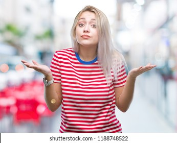 Young blonde woman over isolated background clueless and confused expression with arms and hands raised. Doubt concept.
