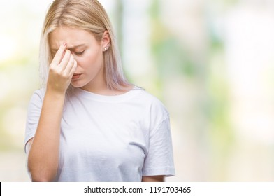 Young blonde woman over isolated background tired rubbing nose and eyes feeling fatigue and headache. Stress and frustration concept.