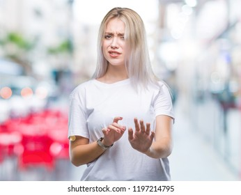 Young blonde woman over isolated background disgusted expression, displeased and fearful doing disgust face because aversion reaction. With hands raised. Annoying concept.