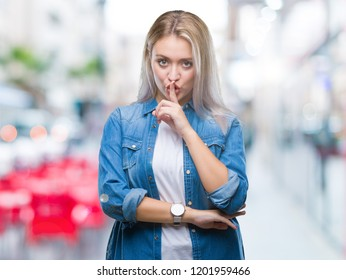 Young blonde woman over isolated background asking to be quiet with finger on lips. Silence and secret concept.