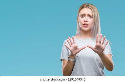 Young blonde woman over isolated background afraid and terrified with fear expression stop gesture with hands, shouting in shock. Panic concept.