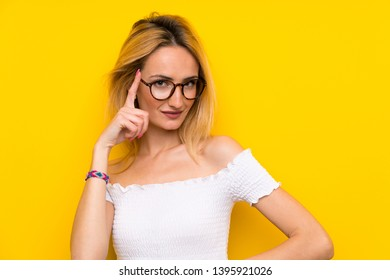 Young blonde woman over isolated yellow wall with glasses