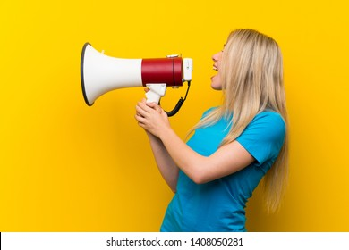 Young blonde woman over isolated yellow background shouting through a megaphone