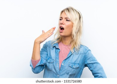 Young blonde woman over isolated white background yawning and covering wide open mouth with hand