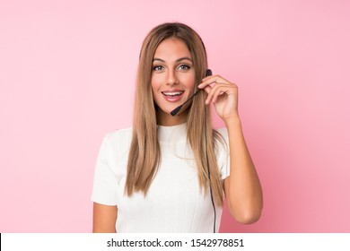 Young blonde woman over isolated pink background working with headset