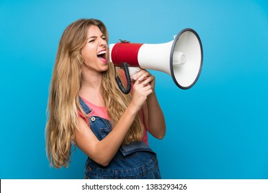 Young blonde woman with overalls over isolated blue wall shouting through a megaphone