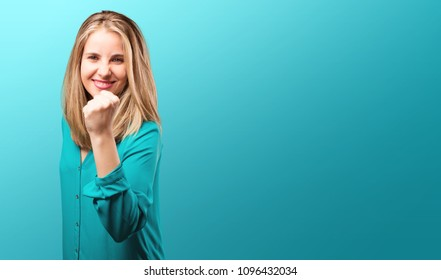 young blonde woman with pink lips gesturing victory or succes and triumph pose. happy expression