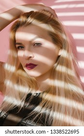 Young blonde woman portrait. Female fashion model. Blinds shadow effect.