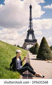 Young blonde woman portrait in front of the Eiffel Tower in Paris, France.