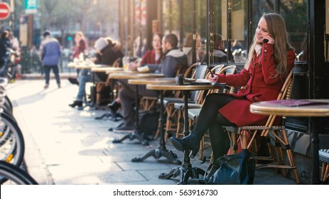 Young blonde woman portrait sit in a typical coffee shop in the city talking at the phone. Paris, France.