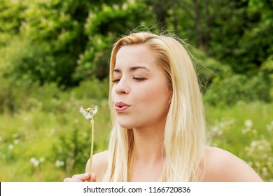Young blonde woman posing with flowers . Outdoor shot.