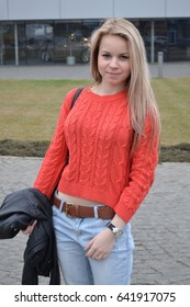 Young blonde woman posing in the street in a red sweater