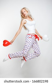 Young blonde woman in pyjamas jumping on gray background with red and white balloons in hands