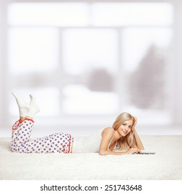 Young blonde woman in pyjamas on white whole-floor carpet reading e-book