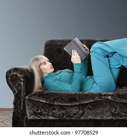 Young blonde woman reading book lying on sofa