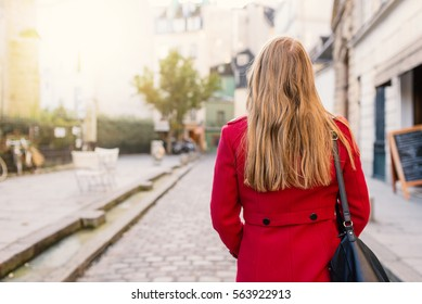 Young blonde woman with red coat portrait walking in the streets of Paris, France. view from behind.