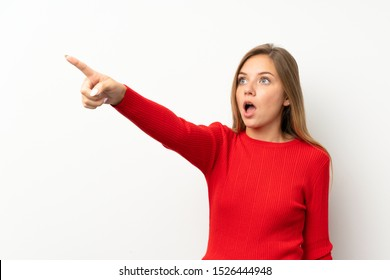 Young blonde woman with red sweater over isolated white background pointing away