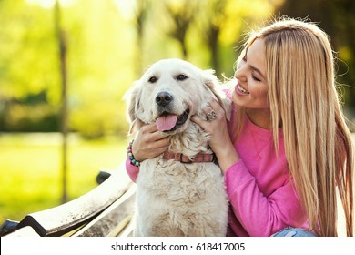 Young blonde woman is relaxing in the park with her dog.
