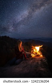 Young blonde woman resting near bonfire outdoor at starry night. Milky Way at mountains. Camp fire on a top of a mountain. Burning fire at dusk on the mountains. Night colorful landscape