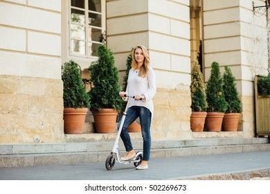 Young blonde woman riding a kick scooter in a European city in the morning