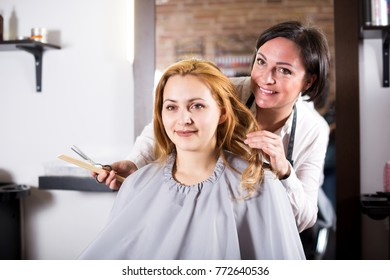 Young blonde woman is satisfied with work of master and her hairdo in hairdress salon