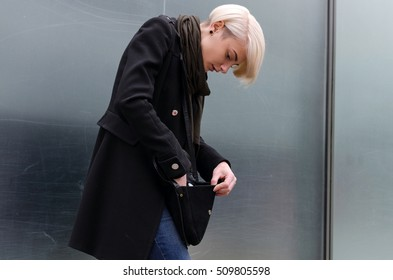 Young blonde woman is searching for something in her bag