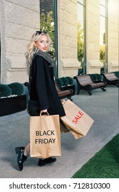 Young blonde woman with shopping bags. Fashionable shopper with Black Friday paperbag going out the mall. Black coat and shoes, sunglasses
