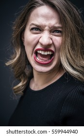 Young blonde woman shouting, yelling or screaming, studio shot on dark grey background