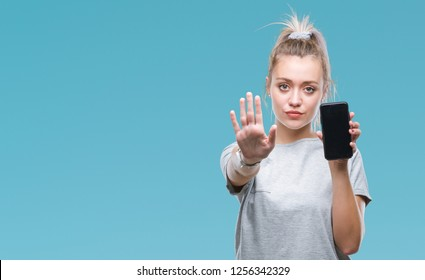 Young blonde woman showing screen of smartphone over isolated background with open hand doing stop sign with serious and confident expression, defense gesture
