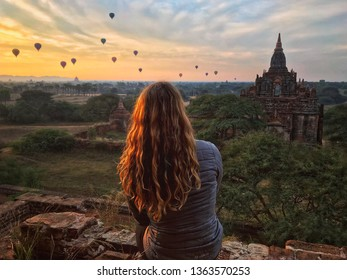 A young blonde woman sits alone at sunrise in Bagan, Myanmar