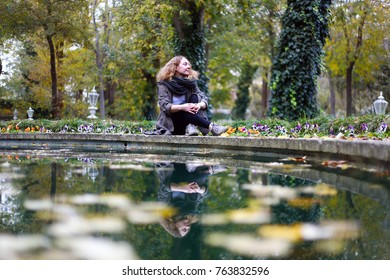 A young blonde woman sits near a pool in autumn.