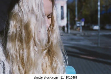 A young blonde woman sitting in a cafe on a street